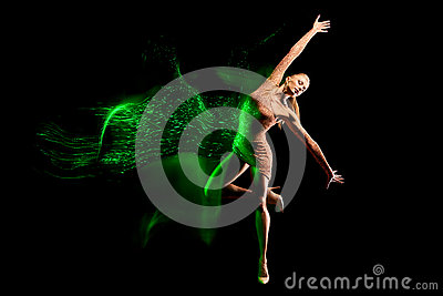 Fine art portrait of beautiful woman dancer in green sparkles