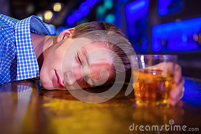 Drunk man lying on bar counter