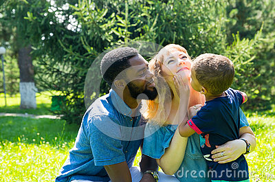 African American happy family: black father, mom and baby boy on nature. Use it for a child, parenting