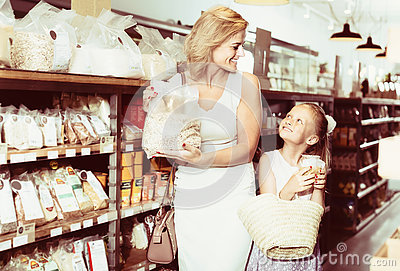 Woman with daughter buying cereals in store