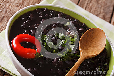 Vegetarian food: spicy black beans close up in a bowl. horizonta