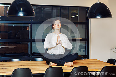 Portrait of slim fit sporty young white Caucasian business woman meditating doing yoga exercises