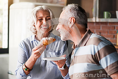 Old man tasting cruassan held by wife in kitchen