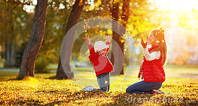 Happy family mother and child girl playing and throw leaves in a
