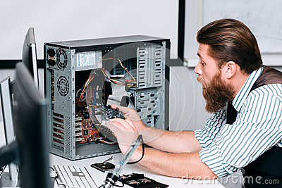 Repairman disassembling computer unit for repair