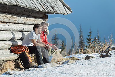Two friends having rest on wooden bench in winter mountains outdoors