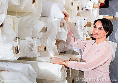 Portrait of happy mature woman with cloth rolls