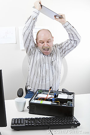 Businessman Banging File On Computer Chassis At Table