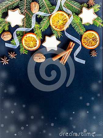 Christmas decoration over dark wood background. Top view of homemade butter nuts star shaped cookies with icing, pine, orange