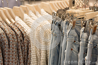 Womens clothes and jeans are hanging on hangers in store