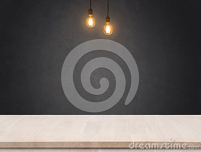 Tungsten light bulb with black cement wall background and wood table.