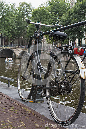 Old bike on the pavement near the canal