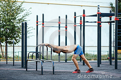 Muscular man warming up before exercise at crossfit ground doing push ups as part of training. Sport concept