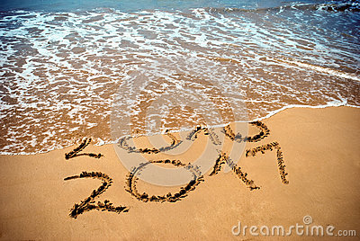 New Year 2017 is coming concept - inscription 2017 and 2016 on a beach sand, the wave is covering digits 2016. New Year 2017 celeb