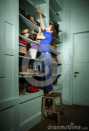 Freckled red-haired little boy searching book on bookcase