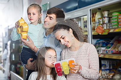 Happy parents with two kids holding purchases in store