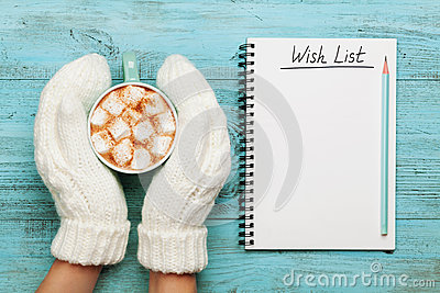 Woman hands in mittens hold cup of hot cocoa or chocolate with marshmallow and notebook with wish list on turquoise vintage