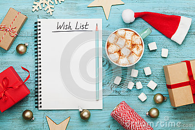 Cup of hot cocoa or chocolate with marshmallow, holiday decorations and notebook with wish list, christmas planning.