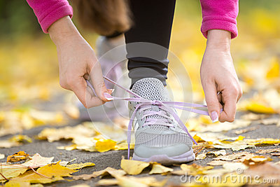 Hands tying trainers shoelaces on the autumn pave