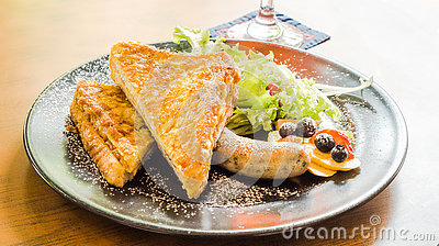 Ham cheese French toast serve with grilled sausage, salad, blueberry, strawberry and topping with icing sugar