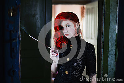 Red-haired girl with red lips in a dark room, a woman holds the mouthpiece with a cigarette in his hand