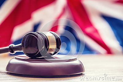 Judges wooden gavel with UK flag in the background. Symbol for jurisdiction