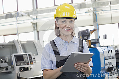 stock image of portrait of smiling female worker using digital tablet in manufacturing industry