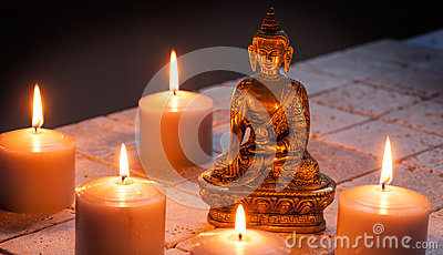 Bronze Buddha with warm lighted candles over limestone background