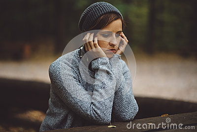 stock image of portrait of sad woman sitting alone in the forest. solitude concept. millenial dealing with problems and emotions.