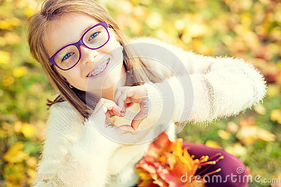 Smiling little girl with braces and glasses showing heart with hands.Autum time