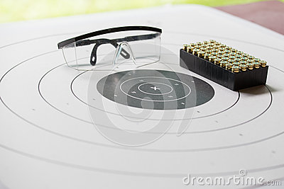 Paper shooting target with safety glasses and 9 mm bullet for sh