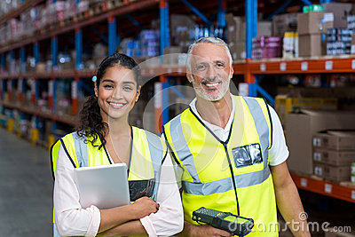 Portrait of warehouse workers standing with digital tablet and barcode scanner