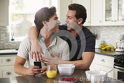 Male gay couple in their 20s embracing in their kitchen