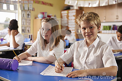 Two kids in a lesson at a primary school look to camera