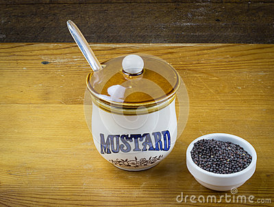 Black mustard seeds and mustard pot on wood table