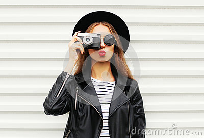 Fashion look, pretty cool young woman model with retro film camera wearing elegant black hat, leather rock jacket over white
