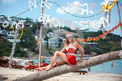 Cute blonde woman in red dress, sunglasses and santa hat sitting on palm tree at exotic tropical beach. Holiday concept