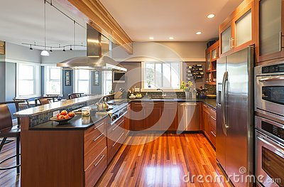 High quality contemporary home kitchen with wood cabinets, hardwood floor, stainless steel appliances, windows and accent lighting