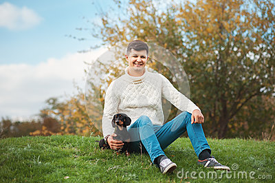 Cute smart dog and his owner young handsome man have fun in the park, conceptions animals, pets, friendship, togetherness