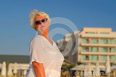Senior grey haired woman staying near building
