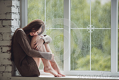 Beautiful young woman sitting alone close to window with rain drops. Sexy and sad girl. Concept of loneliness