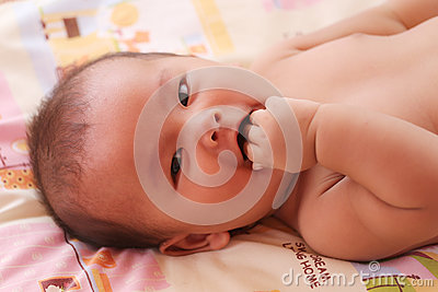 Asian baby smiling happily and have hand sucking on bed.
