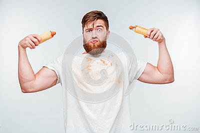 Funny bearded man in filthy shirt holding to hotdogs