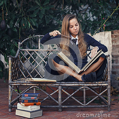 Young witch practicing with magic books. Helloween