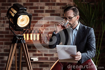 Serious stylish businessman taking a sip of whisky