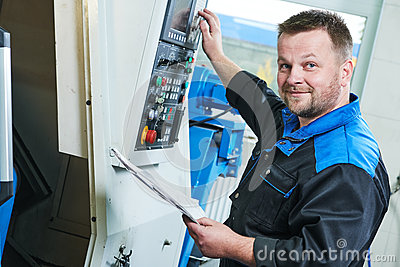 stock image of industrial worker operating cnc turning machine in metal machining industry