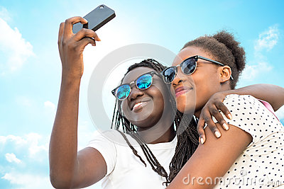 Two diverse african girls taking self portrait with phone.