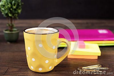 Yellow cup of coffee with white dots. Pretty pink office accessories - notebooks, gold pins, stickers, rubber and polka dot mug