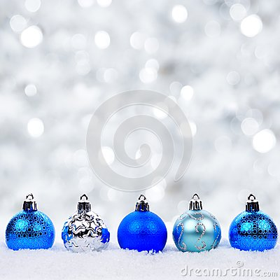 Blue and silver Christmas ornaments in snow with twinkling background