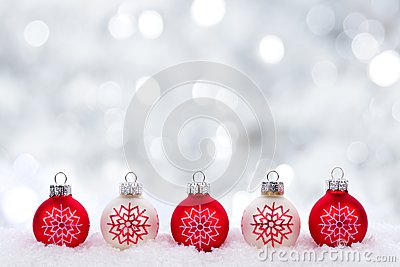 Red and white Christmas ornaments with twinkling silver background
